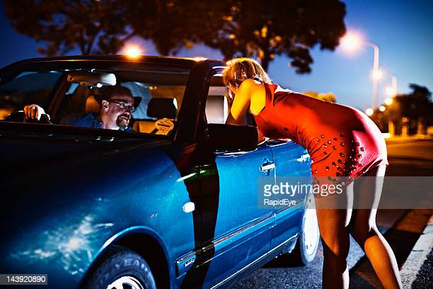 Young prostitute leans into car towards sinister looking man