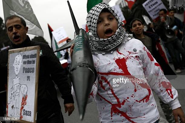 A young protester holds a fake rocket and shouts slogans to express support for the Palestinian cause during a demonstration in Athens on January 10...