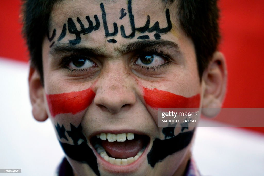 A young protester shouts slogans during a demonstration of supporters of Syrian regime against a possible US military strike on Syria on September 7, 2013 in the southern Lebanese city of Sidon. The boy's face reads in Arabic 'At your service, Syria'.