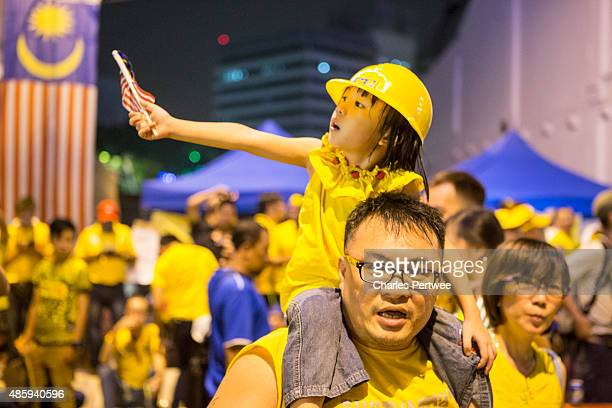 A young protester sits on her fathers' shoulders in a street off Merdeka Square during the Bersih 40 rally on August 30 2015 in Kuala Lumpur Malaysia...