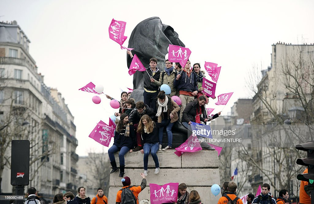 Young protesters on top of a statue hold placards at the start of a march against same-sex marriage, on January 13, 2013 at Denfert-Rochereau square in Paris. Tens of thousands march in Paris on January 13 to denounce government plans to legalise same-sex marriage and adoption which have angered many Catholics and Muslims, France's two main faiths, as well as the right-wing opposition. The French parliament is to debate the bill -- one of the key electoral pledges of Socialist President -- at the end of this month.