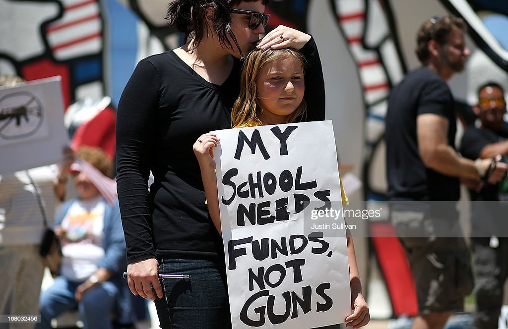 A young protestor is kissed by her mother as she holds a sign during a demonstration in favor of gun regulation outside of the 2013 NRA Annual Meeting and Exhibits at the George R. Brown Convention Center on May 4, 2013 in Houston, Texas. More than 70,000 people are expected to attend the NRA's 3-day annual meeting that features nearly 550 exhibitors, gun trade show and a political rally. The Show runs from May 3-5.