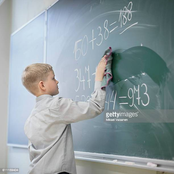 Young pupil standing at chalk board