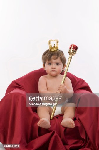 Young queen, 1 year old, sitting on a throne, holding a sceptre