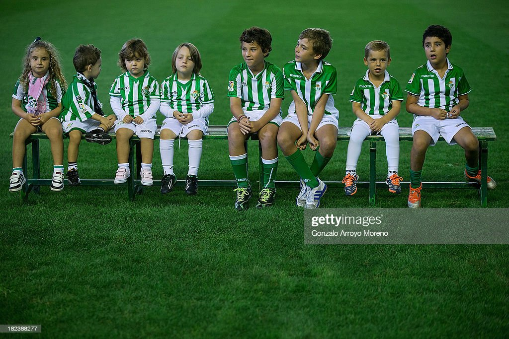 Young Real Betis Balompie fans sit on a bench as the teams line up before start the La Liga match between Real Betis Balompie and Villarreal CF at Estadio Benito Villamarin on September 29, 2013 in Seville, Spain.