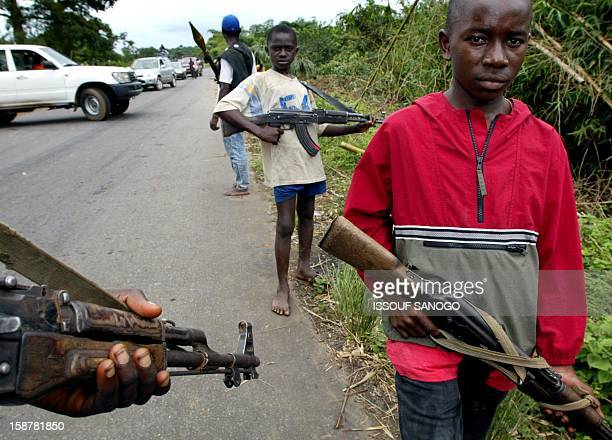 Young rebels of the Liberians United for Reconciliation and Democracy stand guard 19 August 2003 at the southern entry to the river Po bridge where...