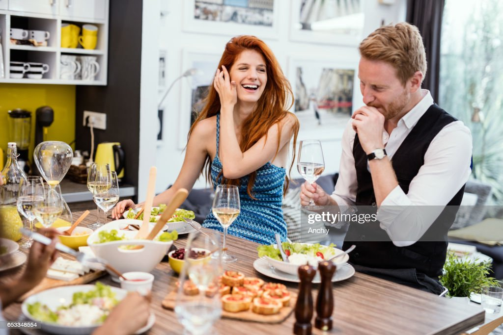 Young red haired couple giggling over dinner. : Bildbanksbilder