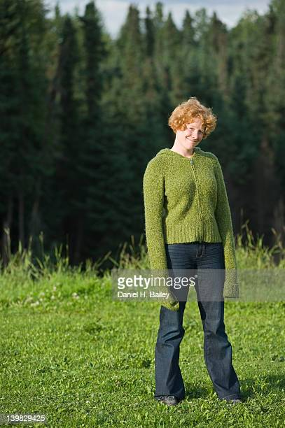 Young red haired woman, 20s-30s, standing in the sunshine, with her sweater sleeves pulled way down over her hands, smiling and being happy and silly