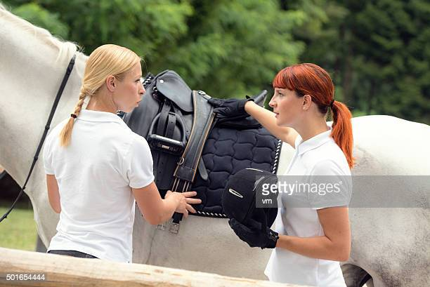 Young red haired woman about to mount a horse