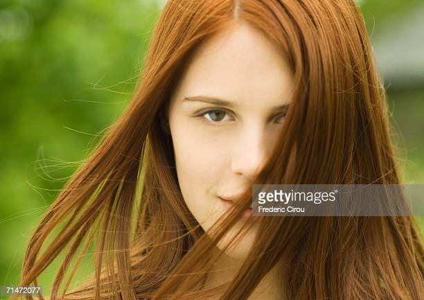 Young red-haired woman with hair blowing in wind