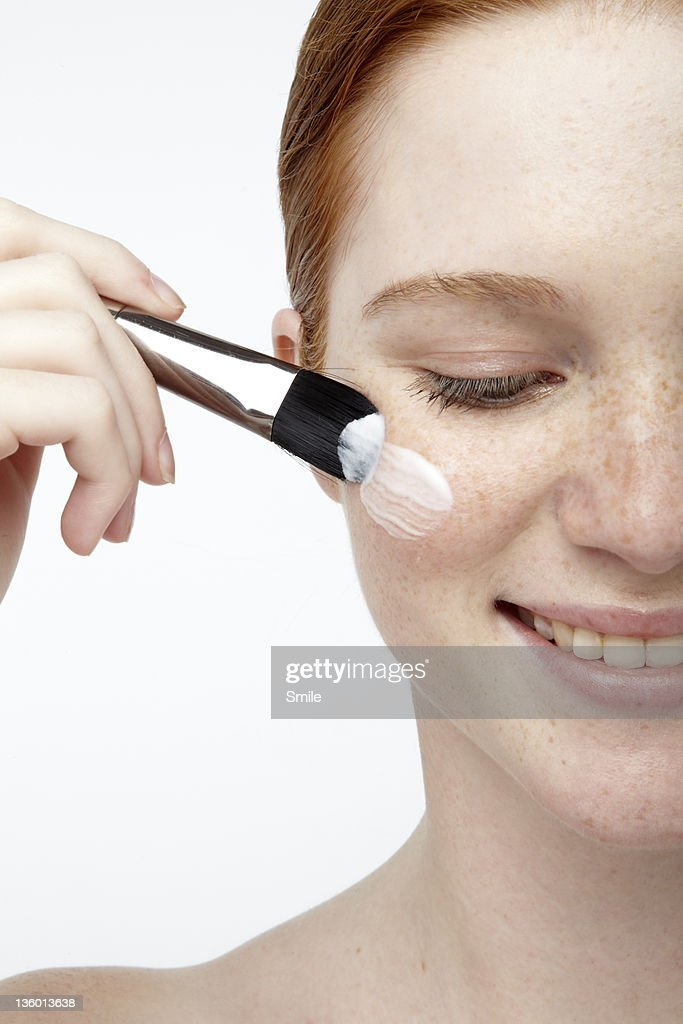 Young redhead applying cream on cheek with brush