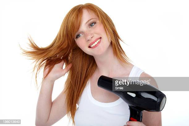 Young redhead blow drying her hair