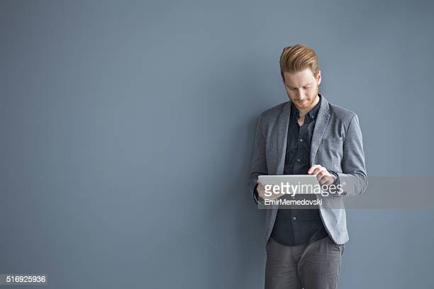 Young redhead businessman working on e-reader against gray wall.