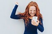Young redhead celebrating good news on her mobile phone cheering and raising her fist in exultation