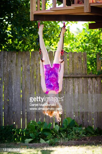 Young redhead girl hanging upside-down : Stock Photo