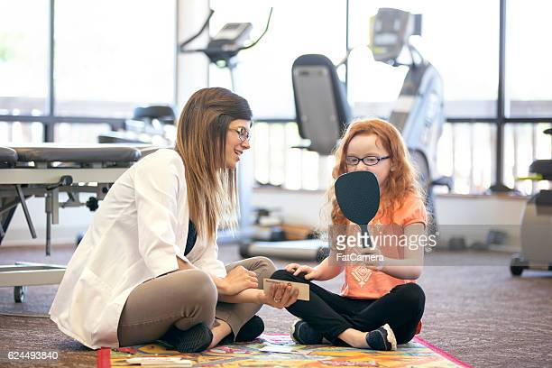 Young redhead girl using mirror for speech therapy