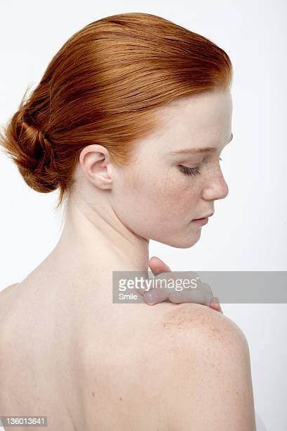 Young redhead rubbing her shoulder