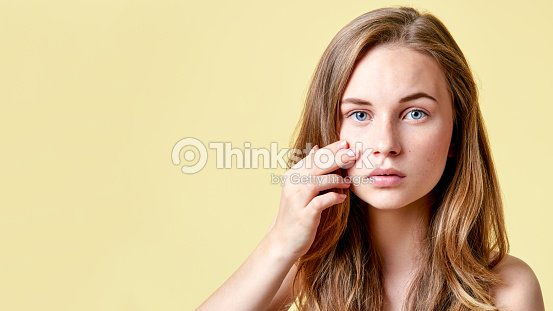 Young redhead teenager with self issues looking into mirror. Girl with low self esteem checking her skin in a mirror. : Stock Photo