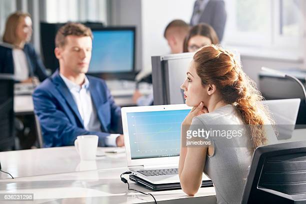 Young, redhead woman at work. Waiting for decisions. Doubts, worries