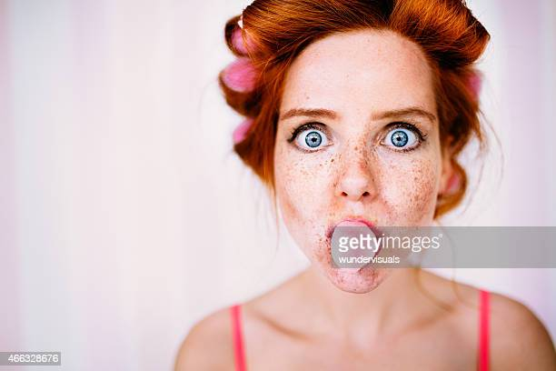 Young Redhead Woman With Curlers In Hair Blows Bubble