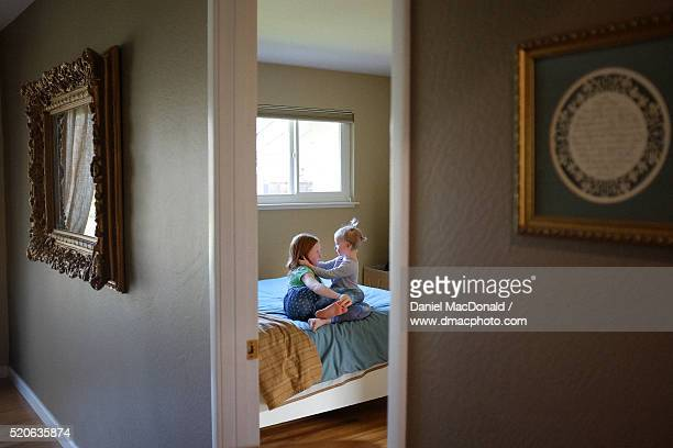 Young redheaded girl and her toddler sister seen through a doorway sharing a quiet private moment in their family home