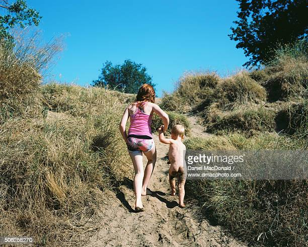 Young redheaded girl helping her toddler sister climb up a sandy riverbank