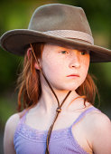 Young redheaded girl in felt hat at sunset