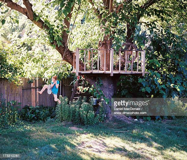 Young redheaded girl on treehouse rope swing