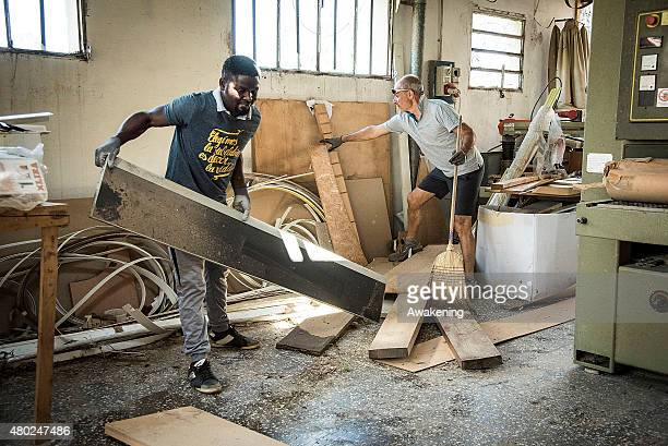 A young refugee and a volunteer help in clearing the damage caused by the tornado which struck the area two days ago on July 10 2015 in Venice Italy...