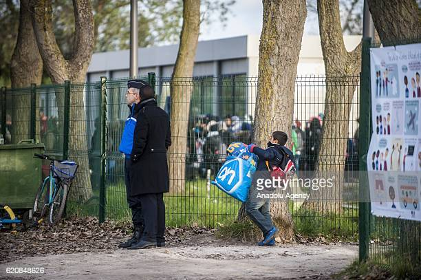 A young refugee carry luggages as he walks to climb into a bus after leaving the 'Jules Ferry' center reception in Calais on November 3 2016 Over 350...