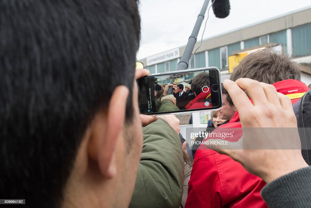A young refugee films French Prime Minister Manuel Valls, as he visits the refugee camp Bayernkaserne (Bavaria barracks) in Munich, southern Germany, on February 13, 2016. / AFP / THOMAS KIENZLE