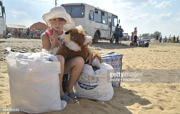 A young refugee from southeast Ukraine waits as she arrives at a refugee camp set up in the Russian border city of Donets'k in the Rostov region on...
