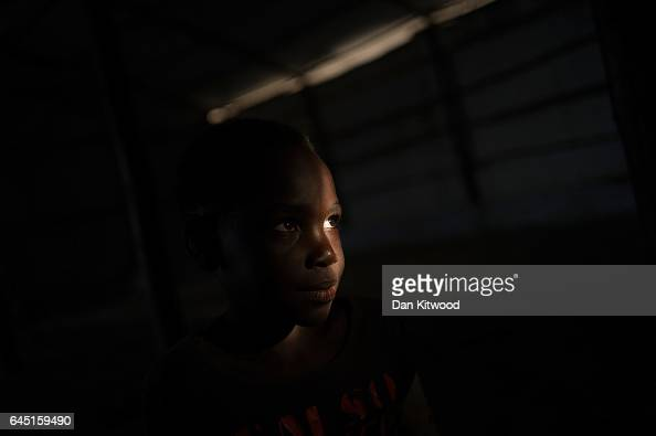A young refugee girl from South Sudan stands in a temporary shelter after being brought from the border by bus on February 24 2017 in Kuluba Uganda...