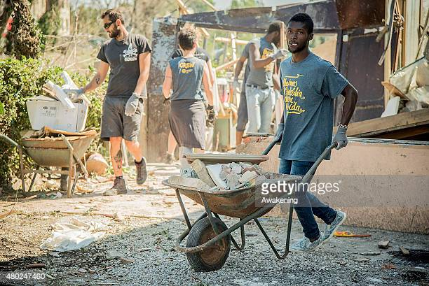 A young refugee helps in clearing the damage caused by the tornado which struck the area two days ago on July 10 2015 in Venice Italy One person died...