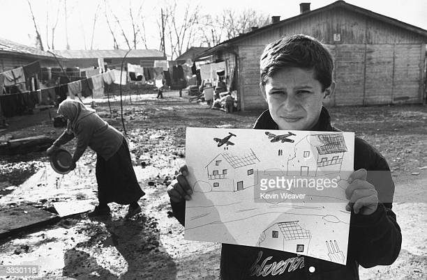 A young refugee holds up a drawing of bombs falling from aircraft onto houses which he drew in his art therapy class at the refugee camp for Bosnian...