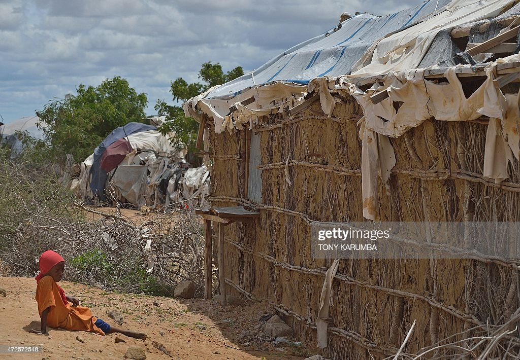 A young refugee sits near a crumbling mudwall along a road as she waits for the arrival of United Nations High Commissioner for Refugees Antonio...