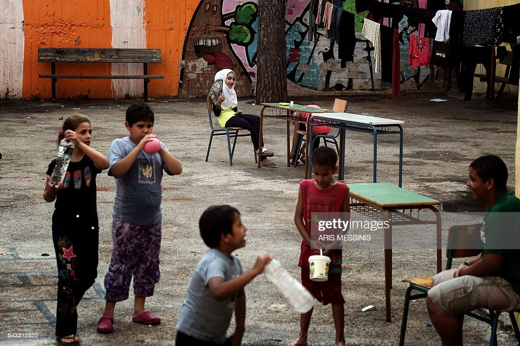 Young refugees play at the yard of an abandoned school used by volunteers for hosting families of refugeees from Syria and Afghanistan in Athens on June 27, 2016. / AFP / ARIS