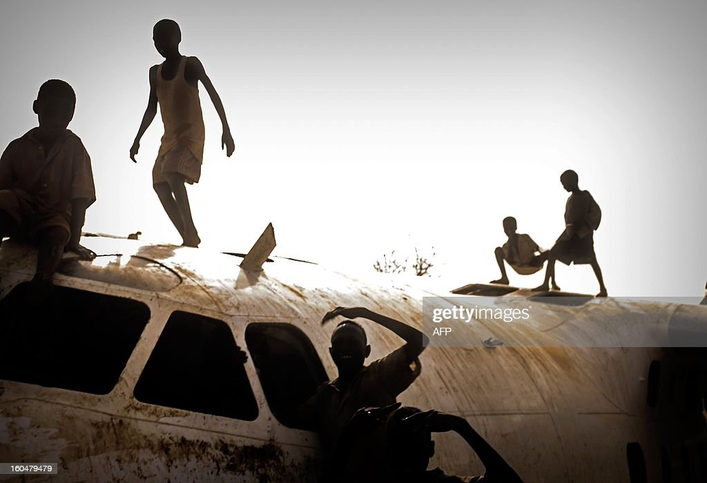 Young refugees play on an aircraft that crashed in November 2012 on the Yida airstrip near the Yida refugee camp in South Sudan, February 1, 2013. The Yida refugee camp houses over 60,000 refugees which have fled from the conflict area of South kordofan in Sudan. AFP PHOTO/Camille Lepage