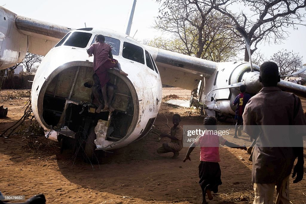 Young refugees play on an aircraft that crashed in November 2012 on the Yida airstrip near the Yida refugee camp in South Sudan, February 1, 2013. The Yida refugee camp houses over 60 000 refugees which have fled from the conflict area of South kordofan in Sudan. AFP PHOTO/Camille Lepage