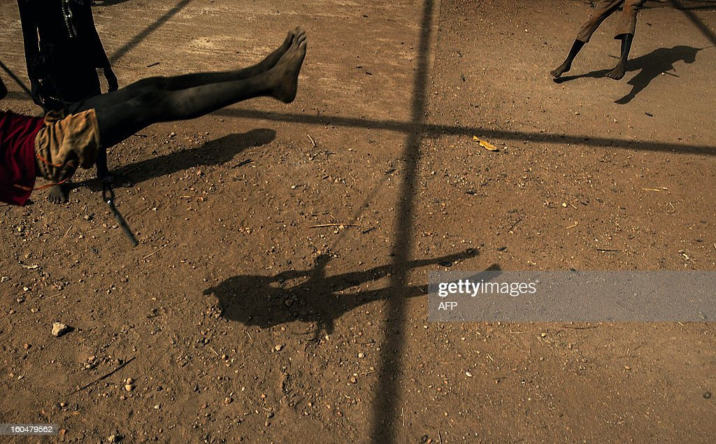 Young refugees play on makeshift swings at the Yida refugee camp in South Sudan, February 1st 2013. The Yida refugee camp houses over 60,000 refugees which have fled from the conflict area of South kordofan in Sudan. AFP PHOTO/Camille Lepage