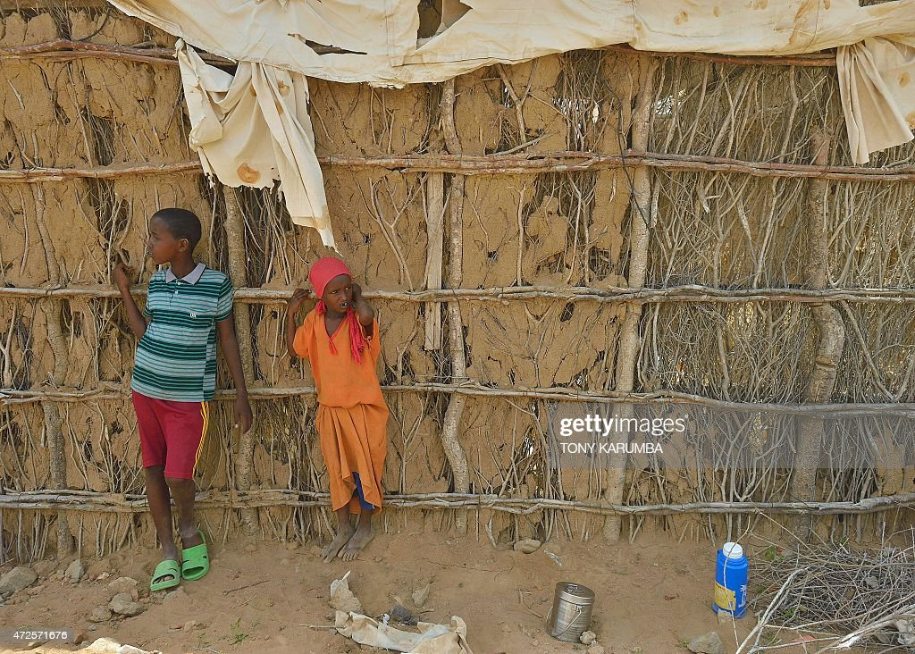 Young refugees stand against a crumbling mudwall along a road as they wait for the arrival of United Nations High Commissioner for Refugees Antonio...