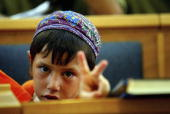A young religious Jewish settler shows his defiance during a farewell ceremony and last ever prayers in the synagogue before leaving Netzarim...