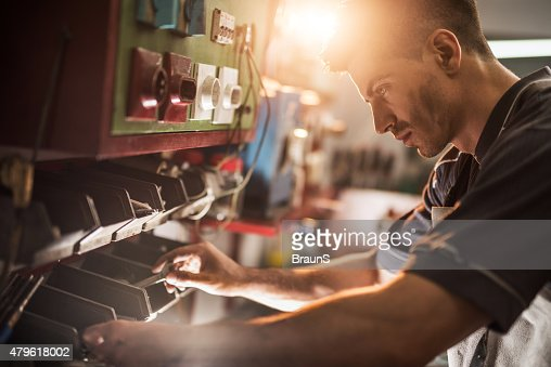 Young repairman choosing the right tool in a workshop.
