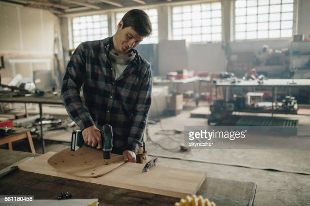 Young repairman working in carpentry workshop and using a drill to repair furniture.