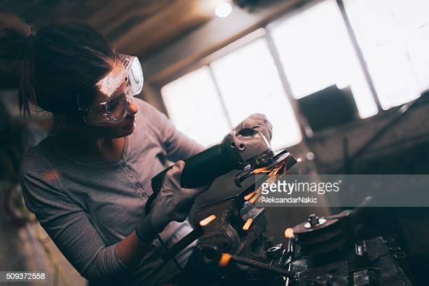 Junge repairwoman mit einer Schleifmaschine