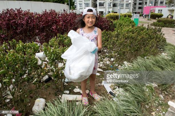 A young resident assists in picking up polystyrene and other rubbish in Heng Fa Chuen in Hong Kong on August 24 a day after Typhoon Hato created a...