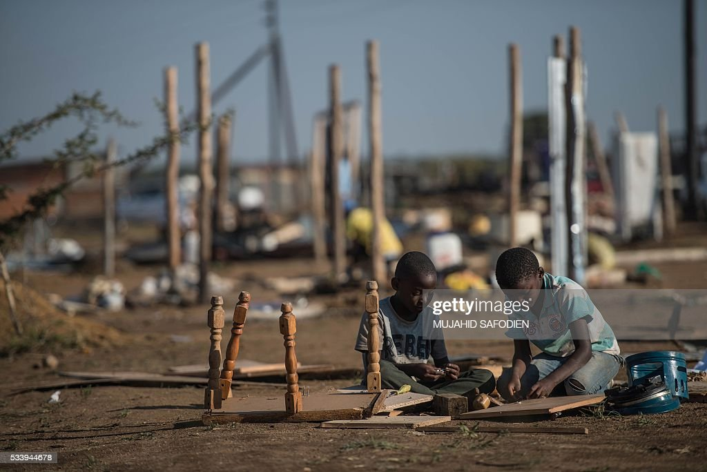 Young residents from the township of Hammanskraal rebuild furnisher as other rebuild their shacks after a forced eviction took place causing violent unrest on May 24, 2016 in Hammanskraal, North of Pretoria. Two people related to the eviction company were reportedly killed on May 23. / AFP / MUJAHID