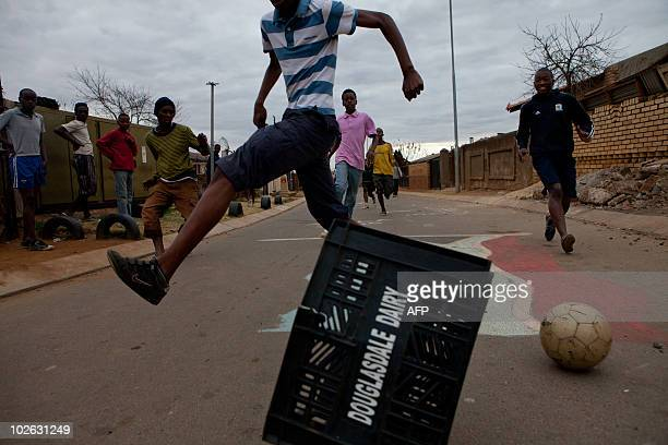 Young residents of the Soweto neighborhood of Jabulani suburban Johannesburg use a milk crate as a goal during a street football game on July 5 2010...