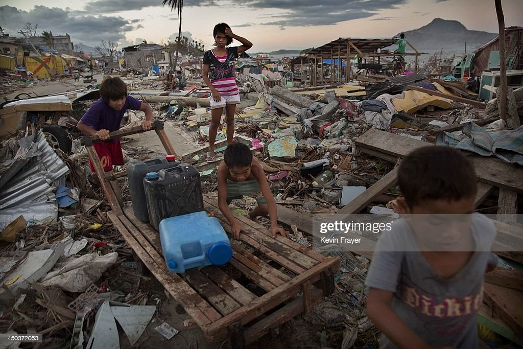 Young residents push a cart as they collect water in an area destroyed in the aftermath of Typhoon Haiyan on November 18 2013 in Tacloban Philippines...