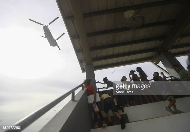 Young residents watch as a US Army helicopter carrying FEMA food and water supplies lands during recovery efforts four weeks after Hurricane Maria...